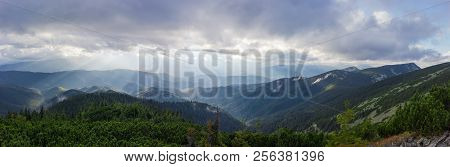 Wide panorama of the ridges, spurs and slopes overgrown with forest illuminated by  sun beams through the clouds in the Carpathian Mountains stock photo