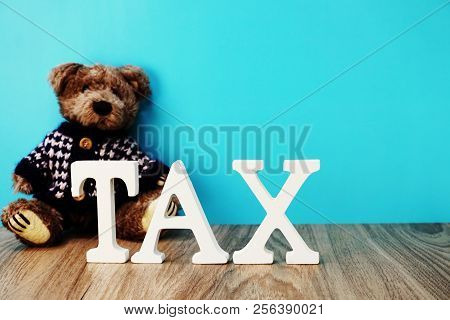 teddy bear and tax alphabet letters on wooden background stock photo