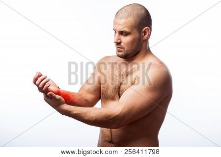 Pain in the wrist.  Young bald man sports physique holds a sick arm on a white isolated background. Fracture of wrist stock photo