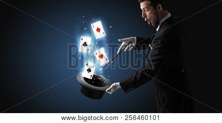 Magician with white gloves conjuring playing cards from a cylinder with magic wand stock photo