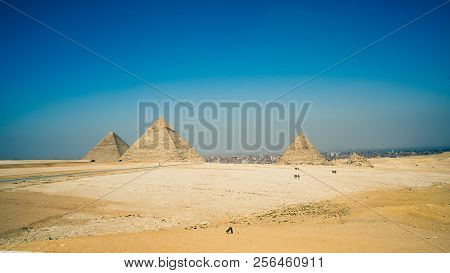 The mysterious old legacy of ancient Egypt - the Greatest wonder of the world, the Egypt pyramids and the stone Sphinx on the Giza platou in endless sands of the Sahara desert stock photo