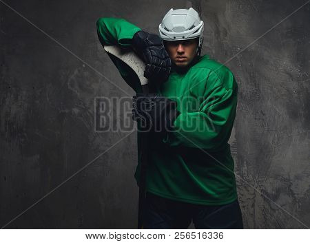 Hockey player wearing green protective gear and white helmet standing with the hockey stick on a gray background. stock photo