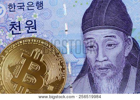 A macro image of a 2000 South Korean won note with a golden physical bitcoin stock photo