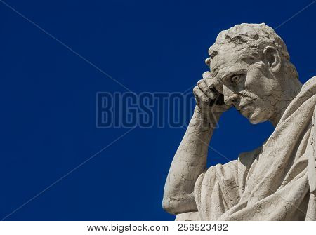 Man statue in the act of thinking against blue sky. Ancient Roman Julian the Jurist statue erected at the end of 19th century in front of the Old Palace of Justice in Rome (with copy space) stock photo