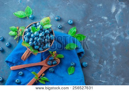 Handmade ceramic cup with blueberries. Ripe and sweet summer berries on a concrete background. Natural beauty, blue and gray palette, copy space stock photo