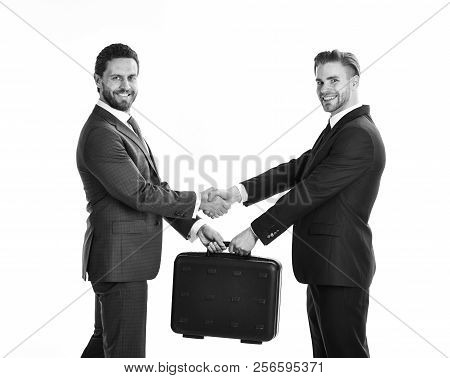 Successful deal concept. Handover of suitcase in hands of partners on white background. stock photo