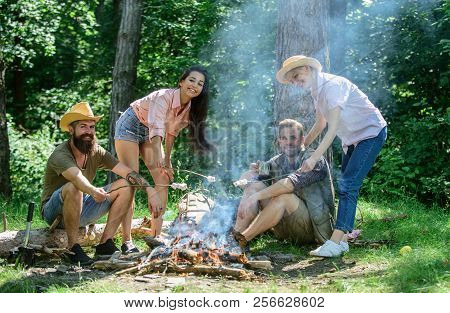 Friends relaxing near bonfire. Friends enjoy picnic eat food nature forest background. Pleasant hike picnic in forest. Company friends or family picnic roasting food. Plan for perfect day hike picnic stock photo