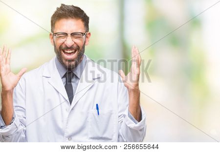 Adult hispanic scientist or doctor man wearing white coat over isolated background celebrating mad and crazy for success with arms raised and closed eyes screaming excited. Winner concept stock photo
