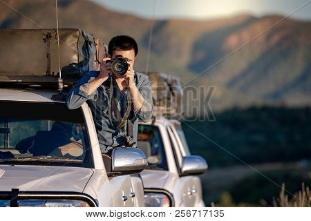 Young Asian male traveler and photographer sitting on the car window taking photo on road trip in Namibia, Africa. Travel photography concept stock photo