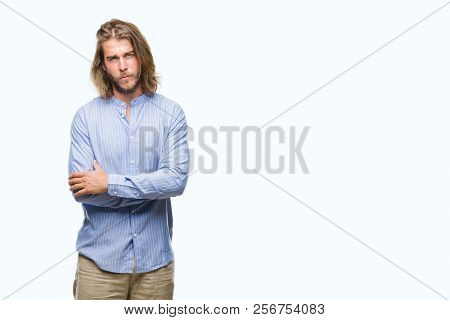 Young handsome man with long hair over isolated background skeptic and nervous, disapproving expression on face with crossed arms. Negative person. stock photo