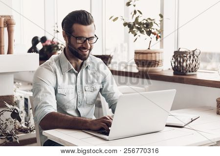 Young Smiling Man Working On Laptop In Cafe. Happy Handsome Bearded Business Man Sitting At Table An