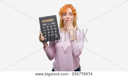 Young redhead woman holding big calculator cover mouth with hand shocked with shame for mistake, expression of fear, scared in silence, secret concept stock photo