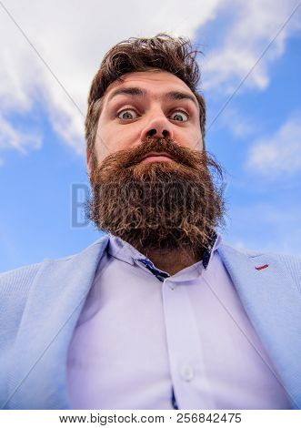 Expert tips for growing moustache. Man bearded hipster with mustache sky background. Ultimate moustache grooming guide. Hipster handsome bearded attractive guy bottom view. Check out my long beard stock photo