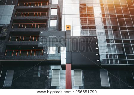 Mock-up of empty urban informational waypoint markers pointing to the left and right made of a black metal; signpost template with a white arrows on it, with an business office building behind stock photo