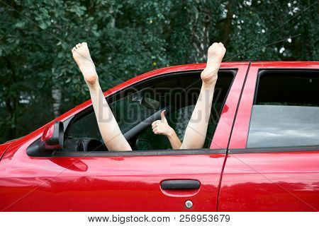 young woman driver resting in a red car, put her feet on the car window and gesturing, happy travel concept stock photo