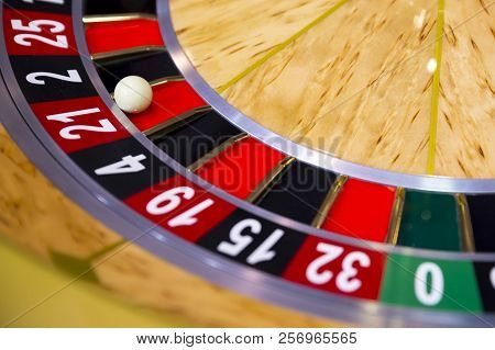 Roulette table in casino. Ball in the rotating gambling machine. Wooden roulette wheel. stock photo