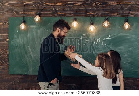 Man with beard in formal suit teaches schoolgirls physics. Teacher and girls pupils in classroom near chalkboard. Curious concentrated children answer question about energy. Physics lesson concept. stock photo