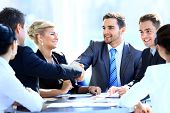 Two business associates shaking hands amid meeting