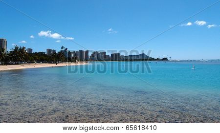 People play at Ala Moana Beach with buildings of Waikiki and iconic Diamondhead in the distance during a beautiful day on the island of Oahu Hawaii. stock photo