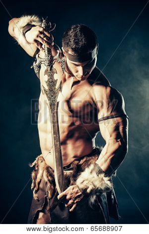 Portrait of a handsome muscular ancient warrior with a sword. stock photo