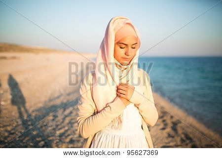 Young beautiful happy muslim woman outdoors portrait.Seaside,beach walk.Beautiful arab saudi woman face posing on the beach praying Allah with the sea in the background stock photo