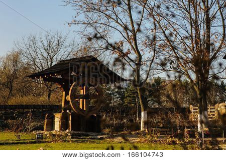 decorative water wood well old antique fountain in the courtyard on a background . landscape design stock photo
