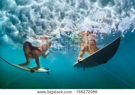 Group of active girls in action. Surfer women with surf board dive underwater under breaking big wave. Healthy lifestyle. Water sport extreme surfing in adventure camp on family summer beach vacation