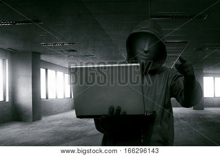 Hacker man with anonymous mask holding laptop while standing against dark room stock photo