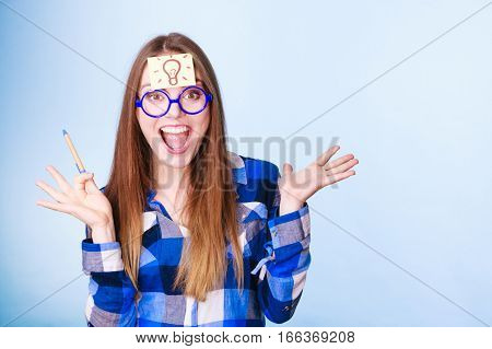 Woman confused thinking seeks a solution paper card with light idea bulb on her head. Excited girl with many ideas celebrates success. Eureka creativity concept studio shot on blue.