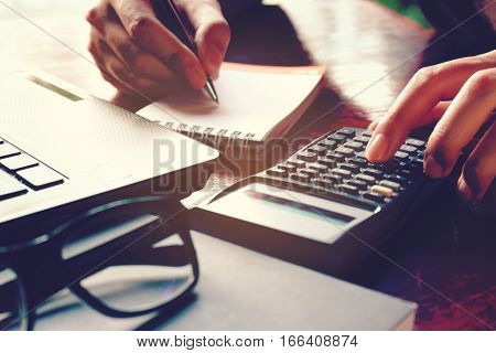 Close Up Woman Hand Using Calculator And Writing Make Note With Calculate About Cost At Home Office.