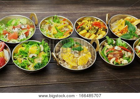 Vegan or vegetarian restaurant dishes above view, hot spicy indian soups, rice and fruit salads in copper bowls. Traditional indian cuisine meal assortment on wood background. Healthy eastern local food