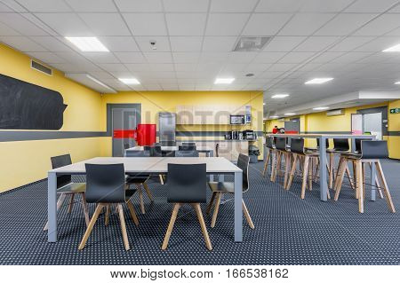 Modern lunchroom interior with wooden tables and black chairs kitchenette in background stock photo