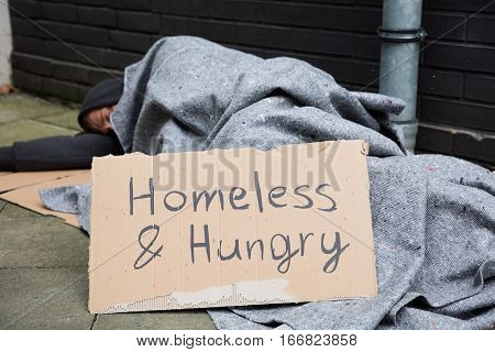 Homeless And Hungry Man Sleeping On Street With Signboard stock photo
