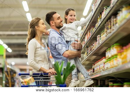 sale, consumerism and people concept - happy family with child and shopping cart buying food at groc