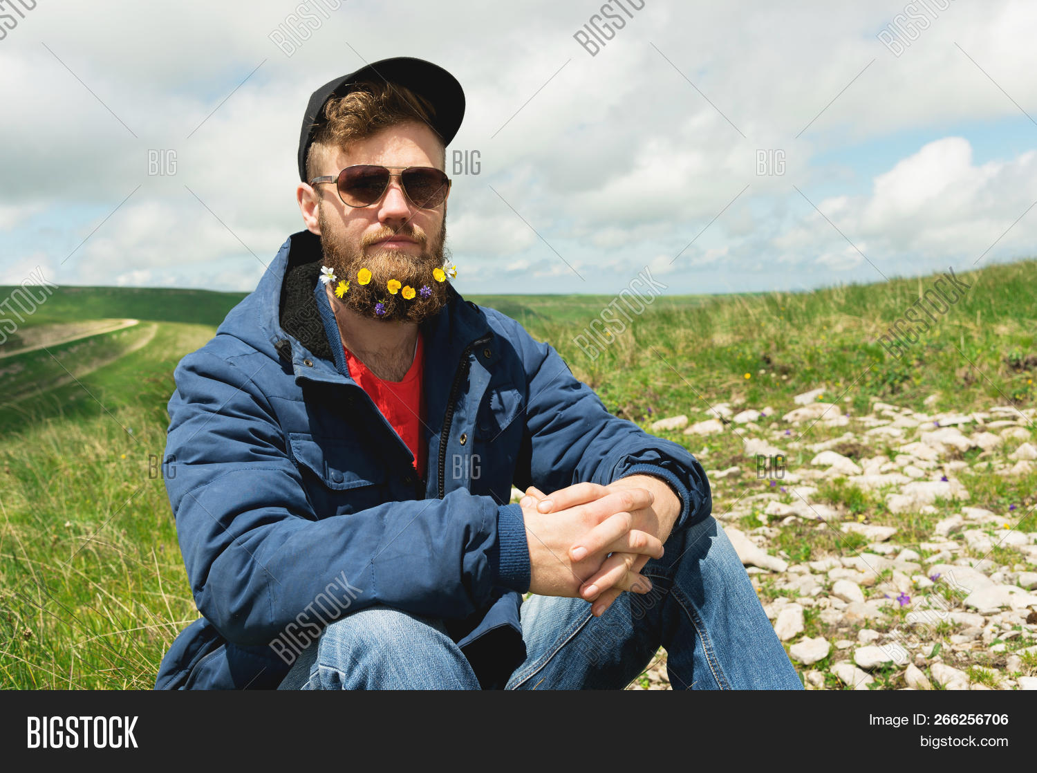 Portrait of a cheerful bearded man in sunglasses and a gray cap with wildflowers in a beard. Soft brutality and good masculinity. Sits in a jacket on the grass in the outdoor