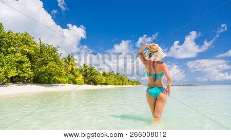 Young attractive woman posing on beach, palm trees, white sand, blue sea and blue sky. Idyllic tropical vacation and summer holiday concept. Inspirational and tranquil beach scene, luxury travel beach destination background stock photo