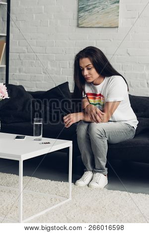 young transgender man sitting on couch at home and looking at pills and water stock photo