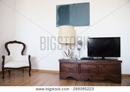 Room with armchair, tv, lamp and white wall. Abstract accommodation. Minimalism in lodging. stock photo
