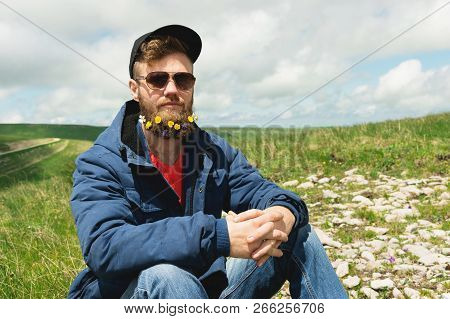 Portrait of a cheerful bearded man in sunglasses and a gray cap with wildflowers in a beard. Soft brutality and good masculinity. Sits in a jacket on the grass in the outdoor stock photo