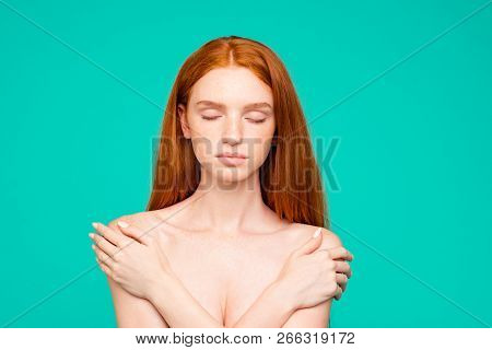Health, body care concept. Portrait of nice perfect nude calm red-haired girl with shiny pure clean fresh smooth flawless skin, embracing herself, closed eyes, isolated over green turquoise background stock photo