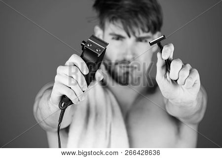 Safety razor and electric shaver or trimmer in hands of blurred handsome man with half shaven face and beard with towel on naked shoulder on blue background. Innovation, archaism. Skincare, grooming stock photo