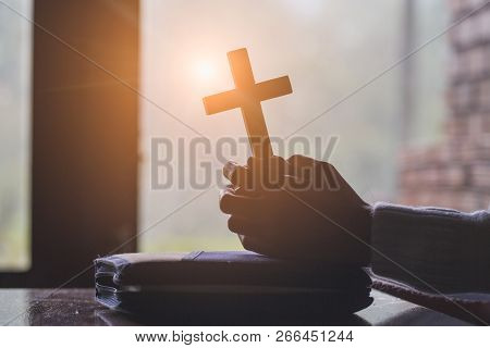 Women pray to God with the Bible and the cross of the morning. Woman Pray for god blessing to wishing have a better life. Christian life crisis prayer to god. stock photo
