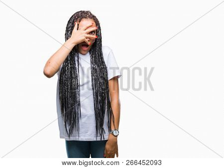 Young braided hair african american girl over isolated background peeking in shock covering face and eyes with hand, looking through fingers with embarrassed expression. stock photo
