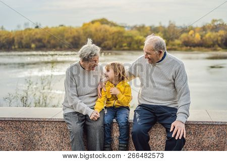 Senior couple with baby grandson in the autumn park. Great-grandmother, great-grandfather and great-grandson stock photo