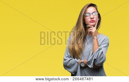 Young beautiful blonde woman wearing glasses over isolated background with hand on chin thinking abo