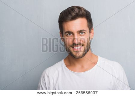 Handsome young man over grey grunge wall with a happy face standing and smiling with a confident smi
