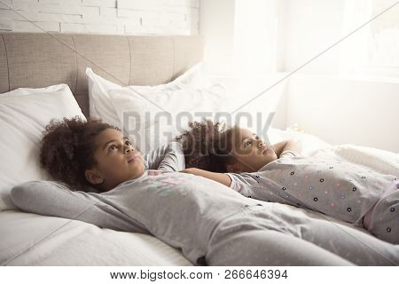 Two little african american girls on bed at home stock photo
