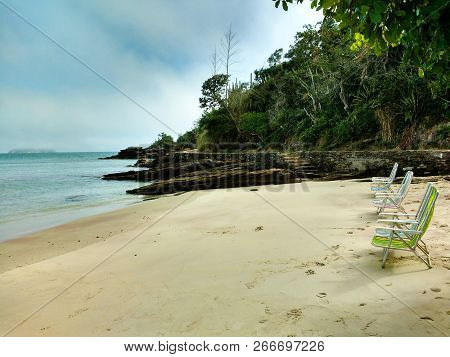 Three colorful beach chairs facing the sea in a paradisiac desert beach in Búzios (Brazil) stock photo