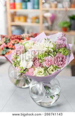 European floral shop. Two Bouquet Mixed beautiful flowers on wooden gray table. Nice garden flowers in the arrangement , the work of a professional florist. stock photo