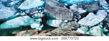 Arctic landscape nature with icebergs tourist manlooking at view of Greenland icefjord - aerial photo. Hikerby ice and iceberg, Ilulissat Icefjord banner panorama. stock photo
